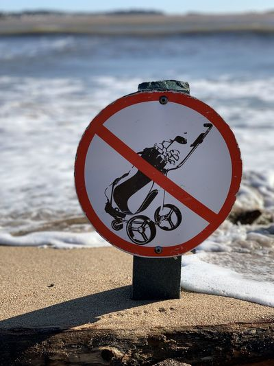 Close-up of sign on beach