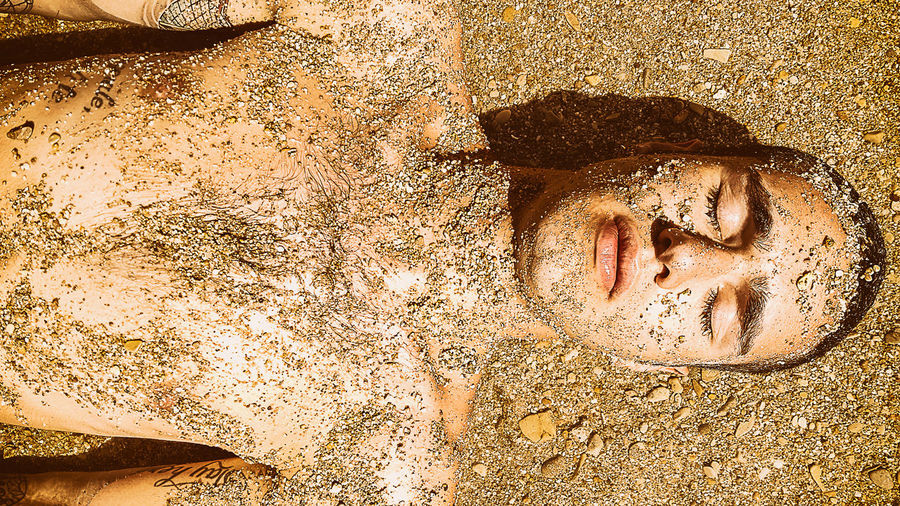Directly above shot of shirtless man with sand lying at beach