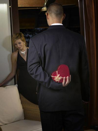 Rear View Of Boyfriend Hiding Gift Box From Girlfriend In Room