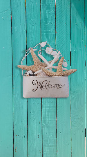 Starfish and seashell welcome basket decor on an aqua blue door in summer on Cape Cod Aqua Cape Cod Coastal Communication Day Decor Nautical Theme No People Outdoors Seashell Starfish  Vertical Welcome Wood Wood - Material