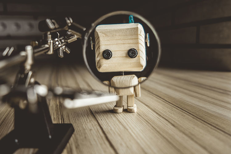 Wooden robot android stands on a table under a magnifying glass. metal clamps with magnifying glass
