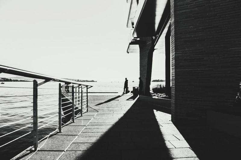 Man on bridge over sea against clear sky