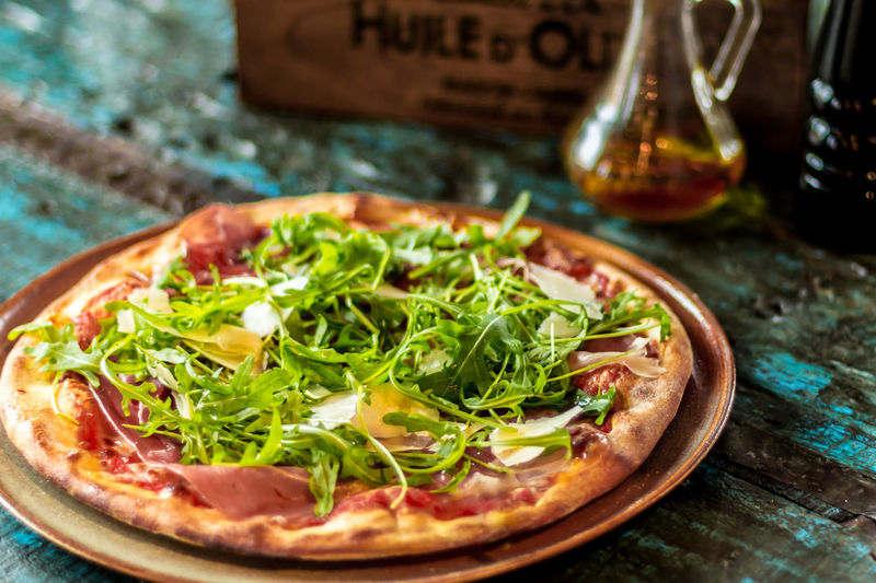 Close-up of pizza with arugula leaves in plate on table