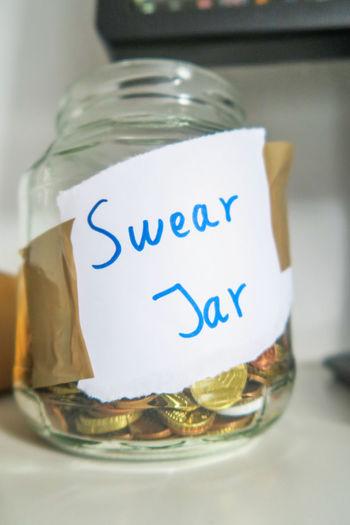 swear jar with coins on a desk next to computer screen Swear Jar Coins Bin Glass