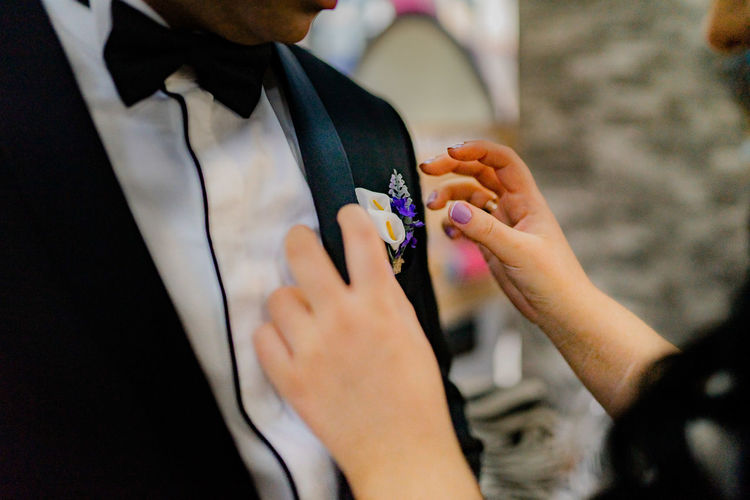 Midsection of woman adjusting groom boutonniere