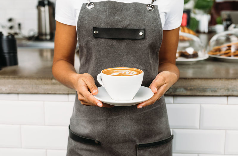 Latte Small Business Waitress Apron Cafe Cafeteria Close-up Coffee - Drink Coffee Cup Front View Holding Indoors  Lifestyles Midsection Occupation One Person Real People Restaurant Service Standing Unrecognizable Person