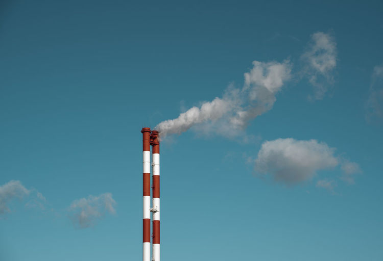 Low angle view of smoke stacks against sky