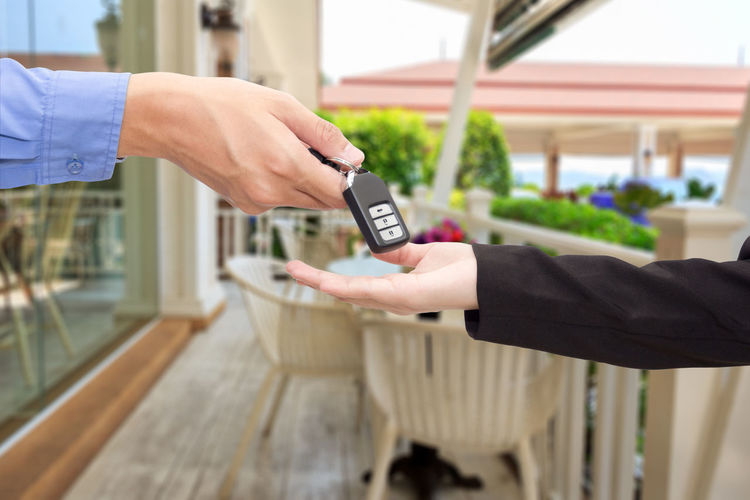 Cropped hand of salesman giving car key to customer outdoors