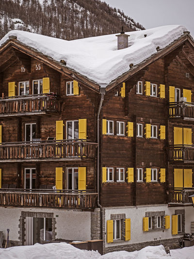 Houses in snow covered with buildings in background