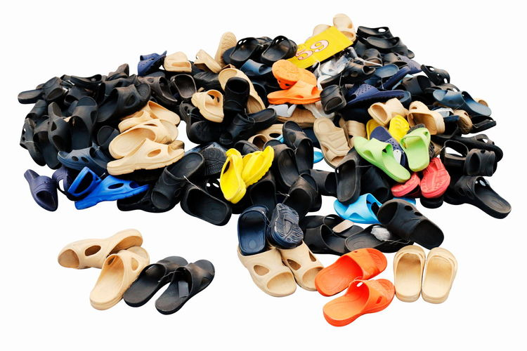 High angle view of multi colored flip flops against white background