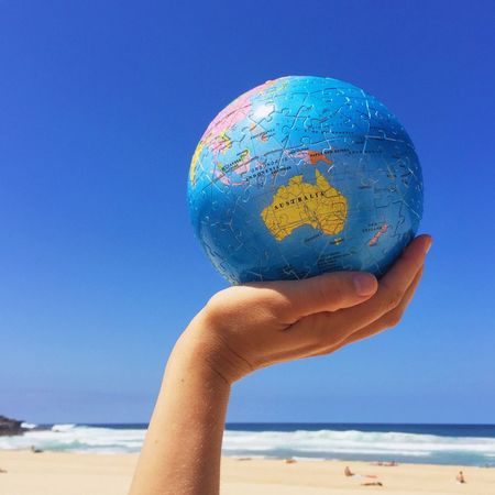 Hand holding a globe Australia Ball Beach Blue Clear Sky Closeup Continent Destination Destinations Earth Globe Hand Holding Planet Sand Scenics Sea Shore Travel Traveling Vacation Vacations Water Waves World
