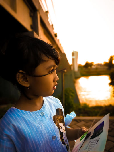 Close-up of thoughtful girl standing against clear sky at sunset