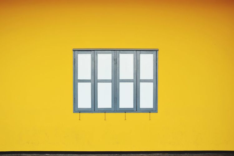 Closed Window Amidst Yellow Wall