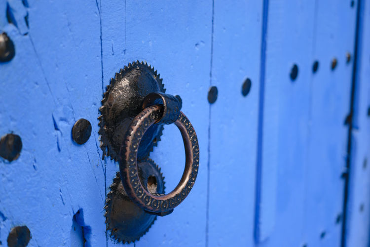 A doorknocker or doorknob on a blue painted old wooden door in Chefchaouen, Morocco. Blue Chefchaouen Classic Close-up Day Door Door Handle Door Knob Door Knocker Doorknob Doorknocker Entrance Gate Handla Knocker Lock Metal No People Old Protection Security Wood