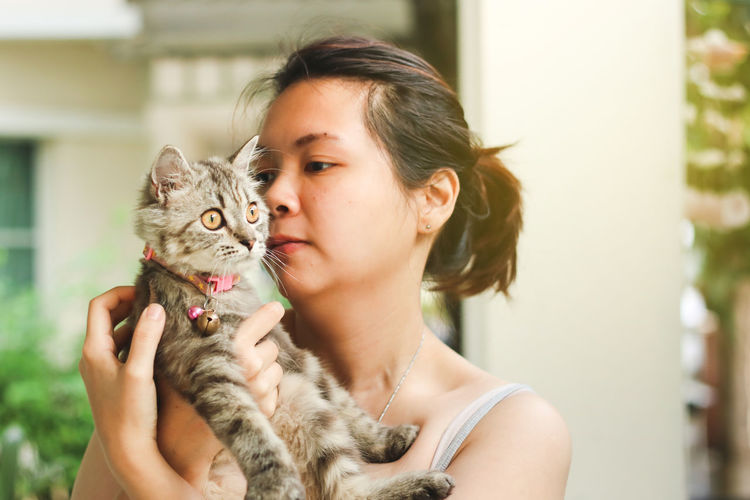 Close-up of woman carrying cat at home