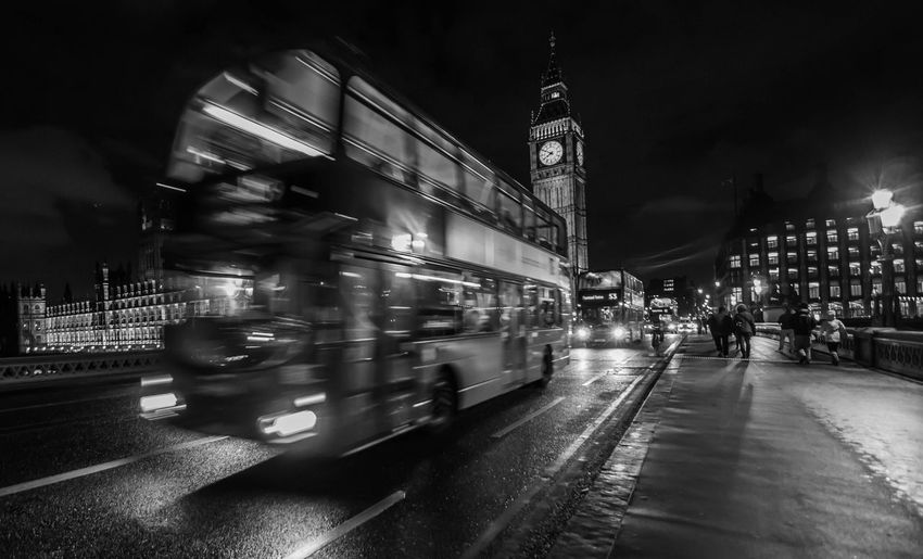 Blurred motion of double-decker bus on westminster bridge in city at night