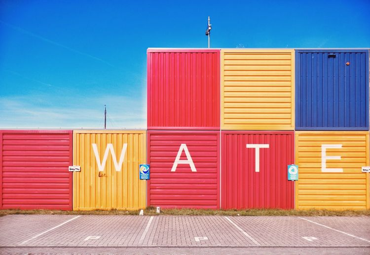 Text On Colorful Cargo Containers At Harbor