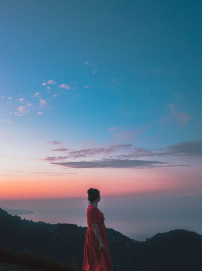 Side view of woman standing sky during sunset