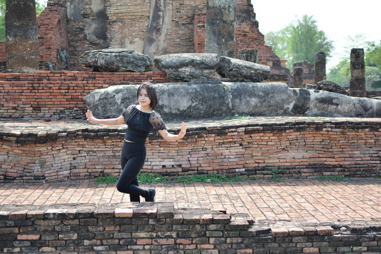 Portrait of young woman with arms outstretched standing on footpath against old ruin temple