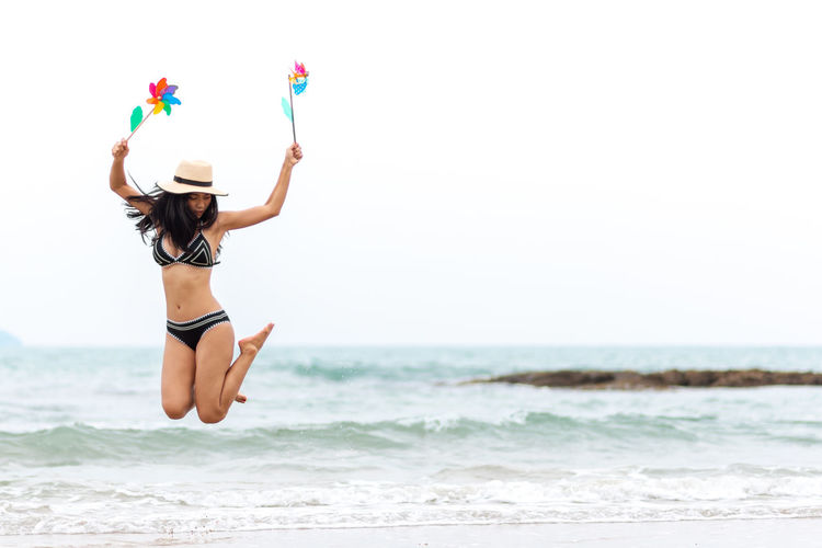 Sea Human Arm Leisure Activity One Person Water Arms Raised Lifestyles Real People Beach Land Limb Motion Horizon Over Water Day Beauty In Nature Nature Women Horizon Outdoors Human Limb Hand Raised Excitement