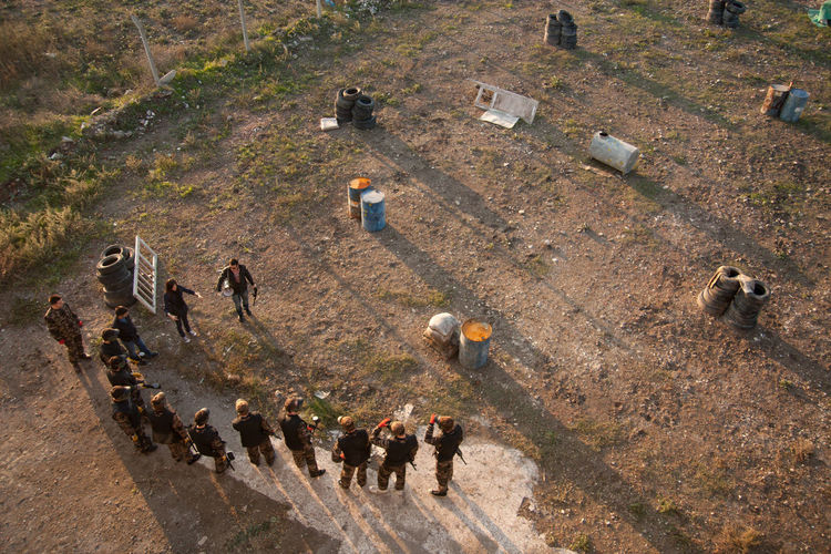 High Angle View Of Paintball Players Preparing And Planning Game On Field