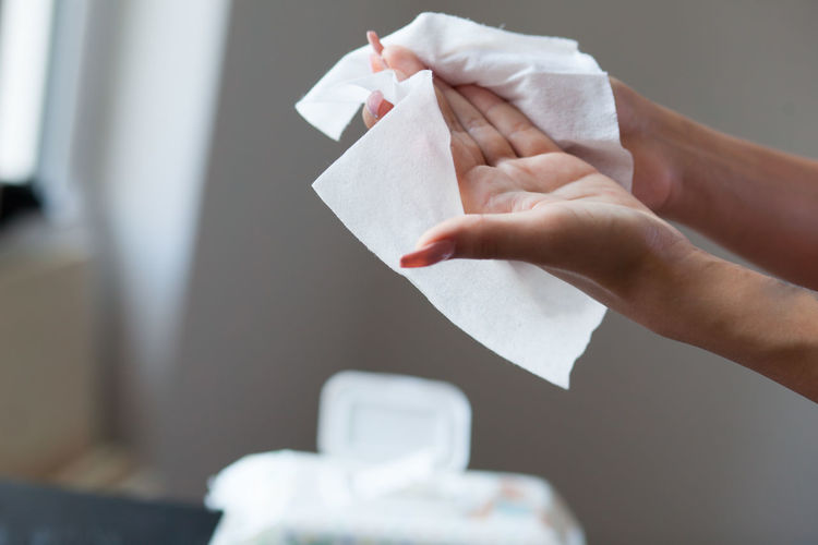 Cropped image of woman cleaning hands with tissue paper at home