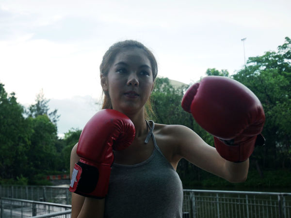 Beautiful Asia girl boxing. Boxing - Sport Boxing Glove Casual Clothing Day Front View Leisure Activity Lifestyles Looking At Camera Nature One Person Portrait Red Sky Sport Sports Clothing Standing Strength Waist Up Young Adult
