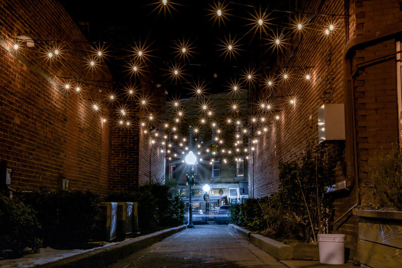 Exterior nighttime long exposure photograph of illuminated alleyway leading to street and coffee shop with starburst effect lights overhead in Cranford, New Jersey, Union County in winter Exterior Leading Lines New Jersey Nighttime Union County College Winter Alleyway Alleyways Architecture Brick Building Building Exterior Cranford Illuminated Long Exposure Longexposure Longexposurephotography Night No People Overhead Passageway Starburst Starburst Effect Street Light