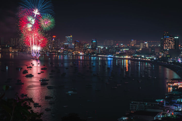Firework display over river and buildings in city at night