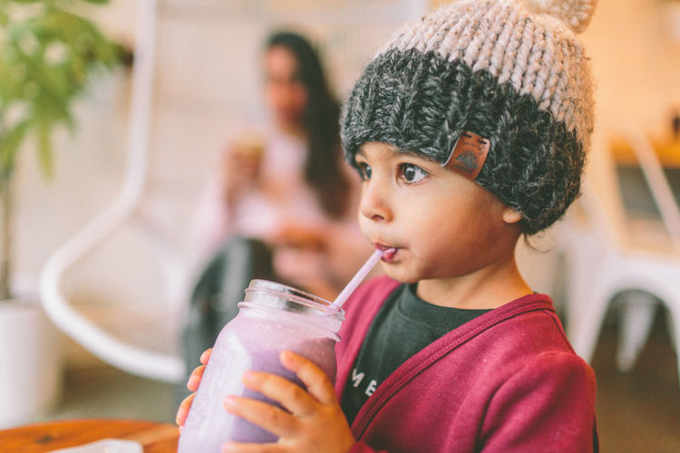 A little Indian boy drinking a smoothie. Child Food And Drink Holding Drink Hat Portrait Close-up Looking Away Cute Drinking Smoothie Indian