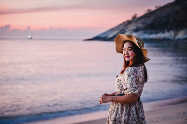 Young woman standing at beach during sunset