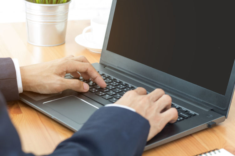 Close-up of man using laptop on table at home