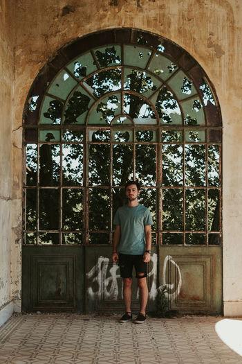 Portrait of man standing against window