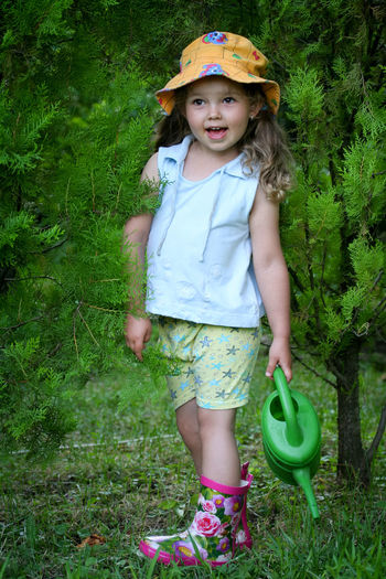Little gardener caught watering plants Childhood Child Plant Grass Girls Women Portrait One Person Full Length Looking At Camera Innocence Front View Nature Standing Smiling Casual Clothing Day Fashion Hairstyle Outdoors Rubber Boot Garden Watering Can Cute