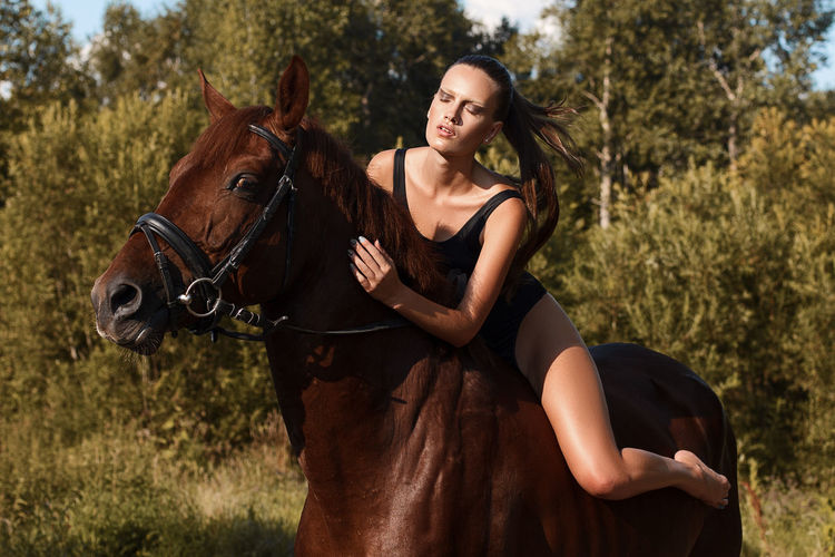 Young Woman Riding Brown Horse On Field