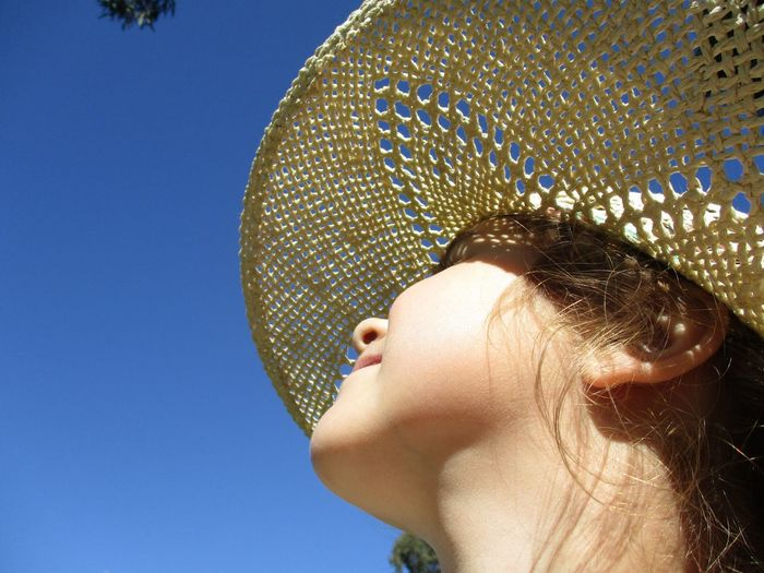 Low angle view of girl wearing straw hat against clear blue sky on sunny day