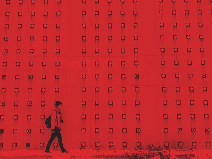 Man walking by red wall of building