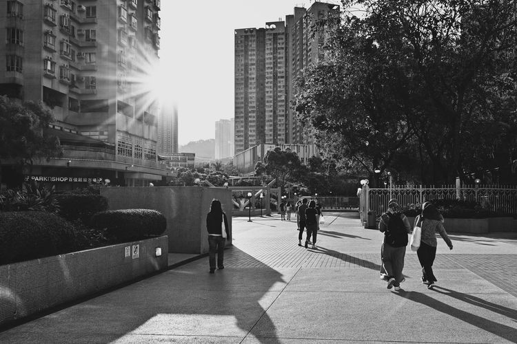People on footpath by buildings in city
