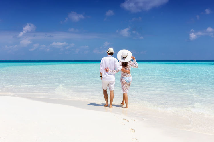 Elegant couple in white summer clothes walks along a tropical beach and enjoys their summer vacation time Sea Sky Horizon Water Beach Land Two People Horizon Over Water Full Length Standing Nature Rear View Real People Beauty In Nature Adult Holiday Togetherness Couple - Relationship Outdoors Women Men White Fashion Elegant Summer Turquoise Colored Maldives Travel Honeymoon Vacations Sun Hug Hat