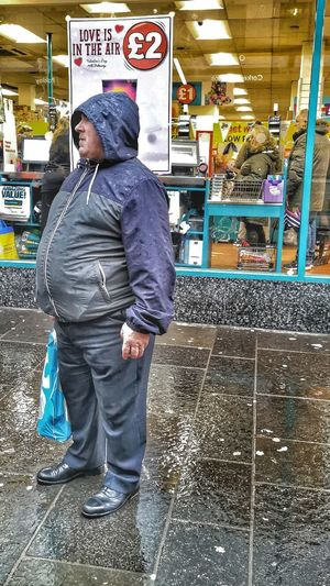 Full length of man with woman walking in rain