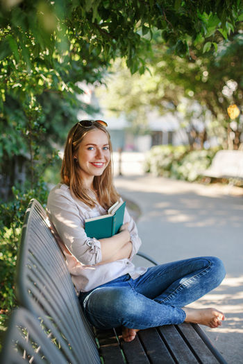 Portrait of happy young woman reading book while sitting on bench at park