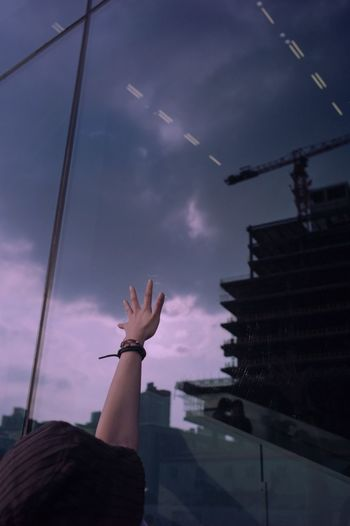 Low angle view of person hand by building against sky
