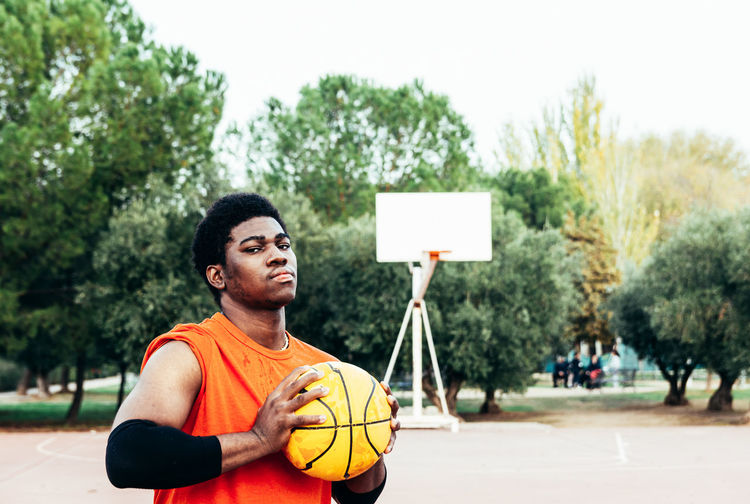Portrait of young man holding basketball at court