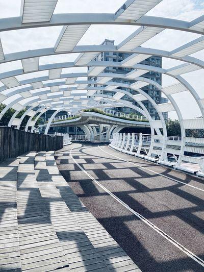 Shadow of bridge on footpath in city