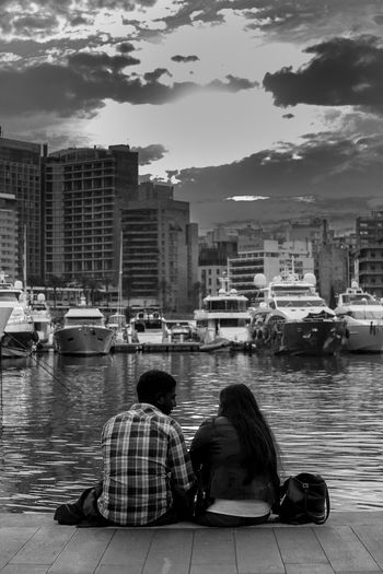 Rear view of couple sitting on boat in river