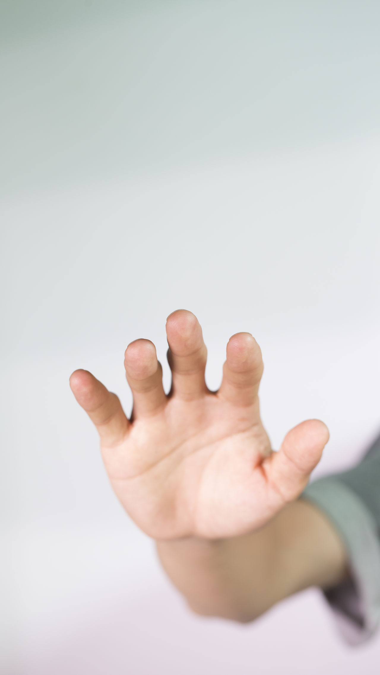 CLOSE-UP OF HUMAN HAND OVER WHITE BACKGROUND