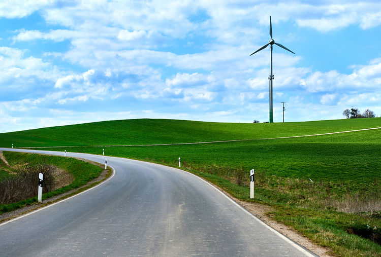 Rural winding road in springtime. Germany. Western Europe Cloudy Sky Conservation Eco Electricity  Energy Production Generator Germany Hills Innovation Landscape Mechanical Power Regenerate Renewable Energy Road Rotate Rotational Energy Rural Sustainable Resources Technology Turbine Western Europe Wind Wind-turbine-construction Windmill