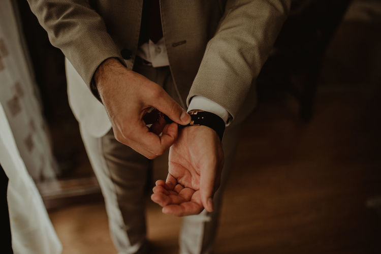 Midsection of bridegroom wearing wristwatch