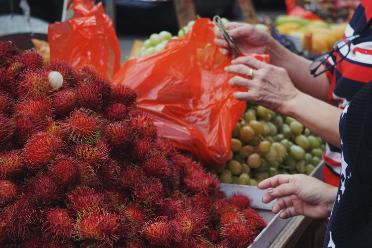 Midsection Of Women Buying Rambutan From Market Stall