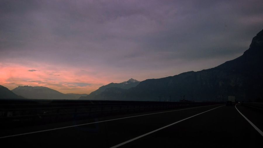 Road by silhouette mountains against sky during sunset